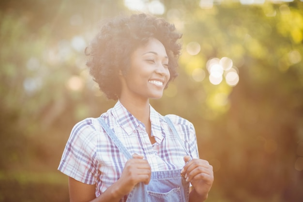 Glimlachende vrouw in de tuin die weg eruit zien Premium Foto