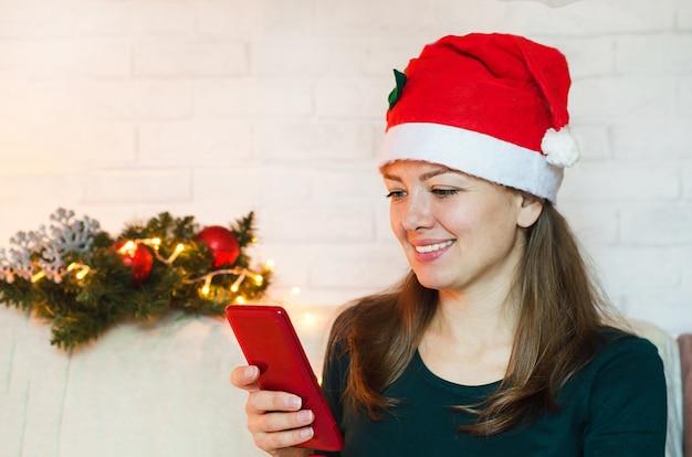 Glimlachende vrouw in kerstmanhoed die mobiele telefoon met behulp van op nieuwjaarsvakantie. Premium Foto
