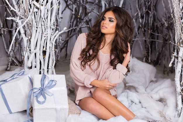 Glimlachende vrouw in warme, gezellige kleding met witte geschenkdoos op winter Gratis Foto
