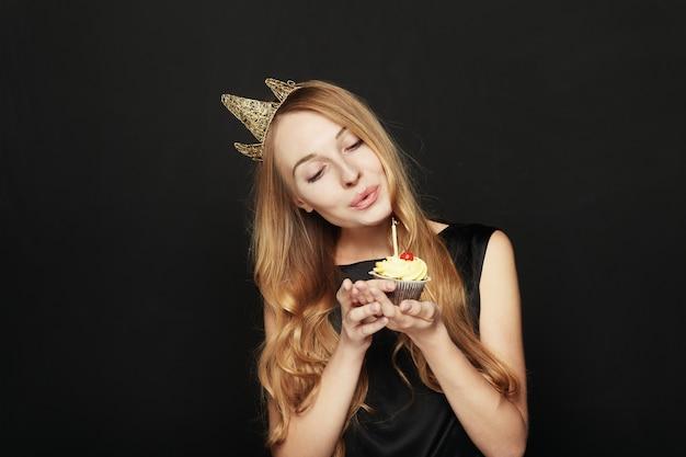 Glimlachende vrouw, met een kroon, die een verjaardag houdt cupcake Gratis Foto