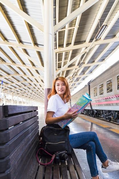 Glimlachende vrouw met kaart, rugzak en camera op bank Gratis Foto