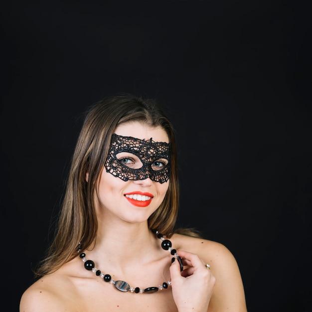 Glimlachende vrouw met parelshalsband die het masker van maskeradecarnaval dragen Gratis Foto