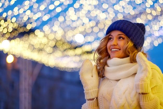 Glimlachende vrouw met slingers en vakantielichten op feestelijke kerstmis of nieuwjaarmarkt. Premium Foto