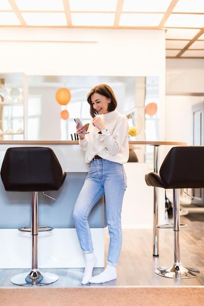 Glimlachende vrouw met telefoon die zich in panoramische keuken met heldere muren hoge lijst bevinden en stoelen Gratis Foto