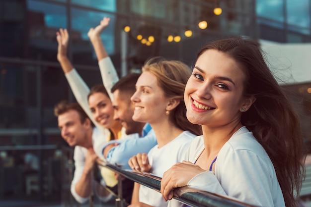 Glimlachende vrouw met vrienden op achtergrond Gratis Foto