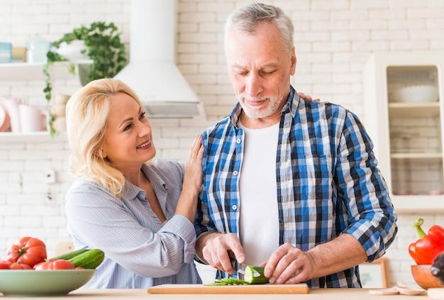 Glimlachende vrouw ondersteunend haar echtgenoot die de komkommer met mes op lijst in de keuken snijdt Gratis Foto