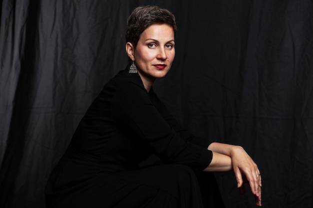 Glimlachende vrouw op middelbare leeftijd met een kort kapsel. portret op een zwarte achtergrond. Premium Foto