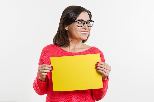 Glimlachende vrouw van middelbare leeftijd met gele vel papier Premium Foto