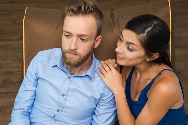 Glimlachende vrouw vraagt peinzende man over iets Gratis Foto