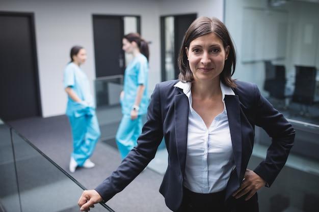 Glimlachende vrouwelijke arts in het ziekenhuisgang Gratis Foto