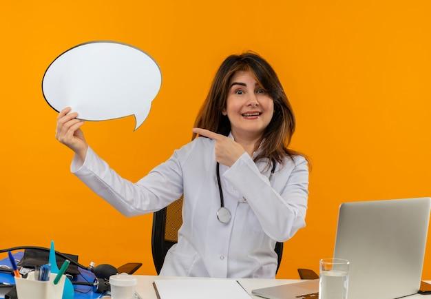 Glimlachende vrouwelijke arts van middelbare leeftijd die medische mantel met stethoscoop zittend aan bureau werkt op laptop met medische hulpmiddelen houden en wijst naar praatjebel op oranje muur Gratis Foto