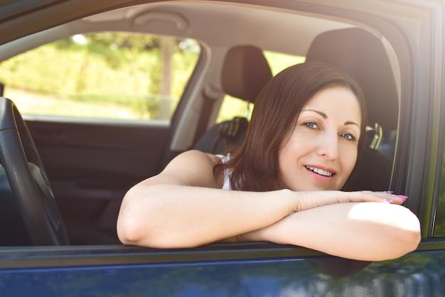Glimlachende vrouwelijke bestuurder die uit de auto kijkt. een portret van een glimlachende vrouw die in de auto zit, kijkend naar de camera. Premium Foto