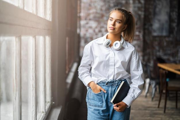 Glimlachende vrouwelijke student in een wit overhemd en draadloze koptelefoon staat voor het raam. Premium Foto