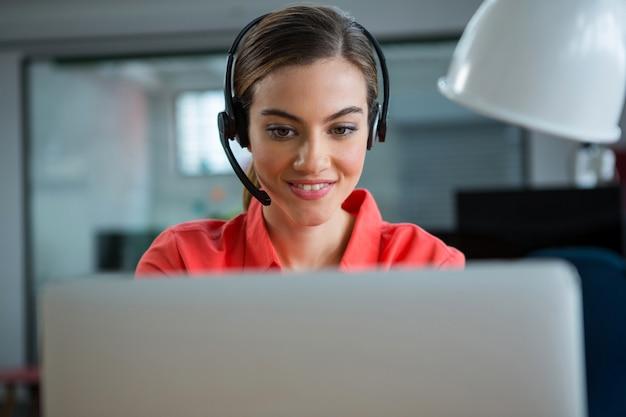 Glimlachende vrouwelijke uitvoerend die aan haar laptop werkt tijdens het bellen Premium Foto