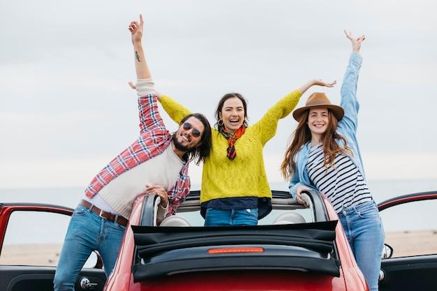 Glimlachende vrouwen dichtbij de gelukkige mens met upped handen die uit auto leunen Gratis Foto