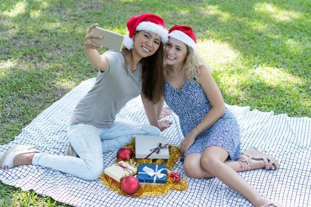 Glimlachende vrouwen die selfie foto met kerstmisgiften op gras nemen Gratis Foto