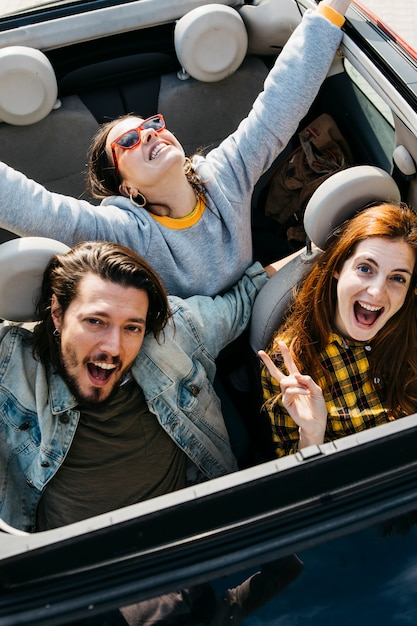 Glimlachende vrouwen en positieve man zitten in de auto Gratis Foto