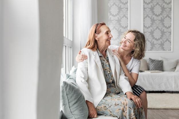 Glimlachende vrouwenzitting op venstervensterbank met haar oma thuis Premium Foto