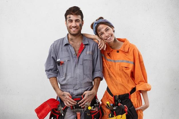 Glimlachende vuile vrouw leunt op de schouder van de monteur van de man, helpt hem om de auto op de werkplek te repareren Gratis Foto