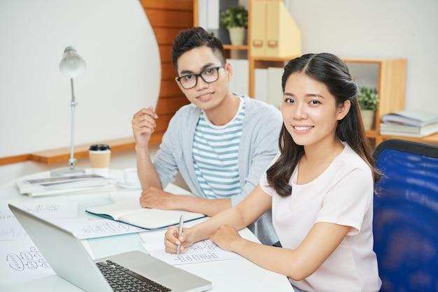 Glimlachende werkende man en vrouw bij bureau Gratis Foto