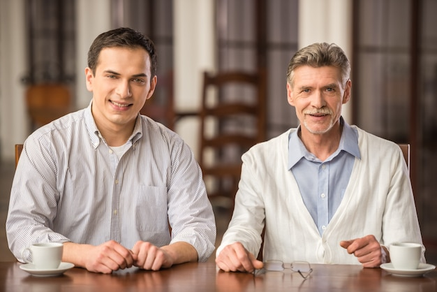 Glimlachende zakenlieden die in overhemden bij de houten lijst zitten. Premium Foto