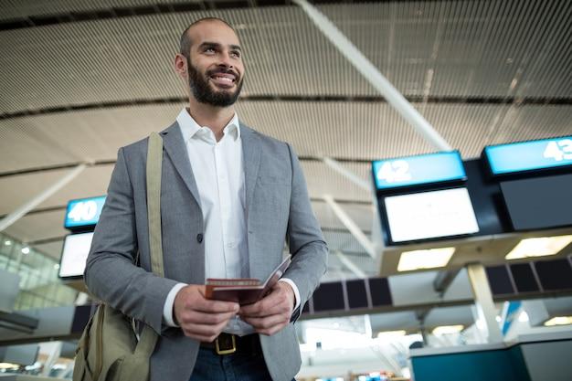 Glimlachende zakenman die een instapkaart en een paspoort houdt Gratis Foto