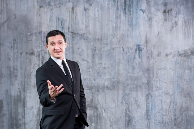 Glimlachende zakenman die op camera richten terwijl status tegen grijze muur Gratis Foto