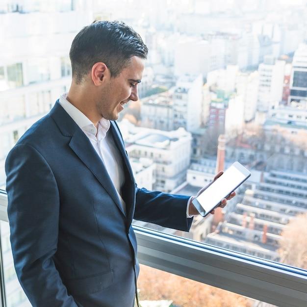 Glimlachende zakenman die smartphone bekijkt Gratis Foto