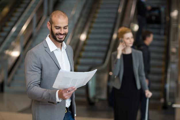 Glimlachende zakenman die zich bij wachtruimte bevindt die de krant leest Gratis Foto