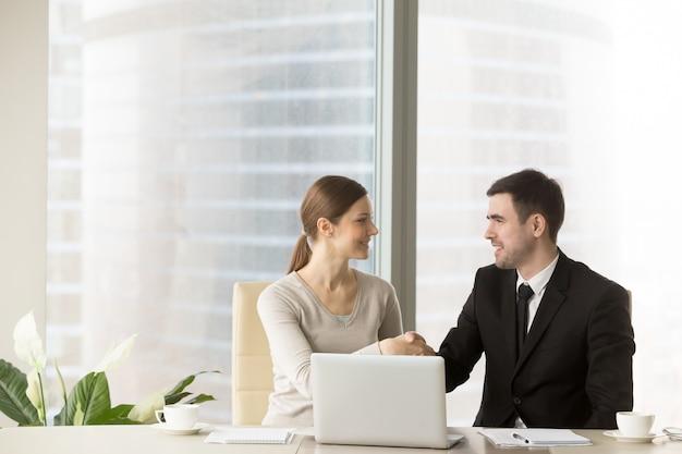 Glimlachende zakenman het schudden handen met onderneemster Gratis Foto