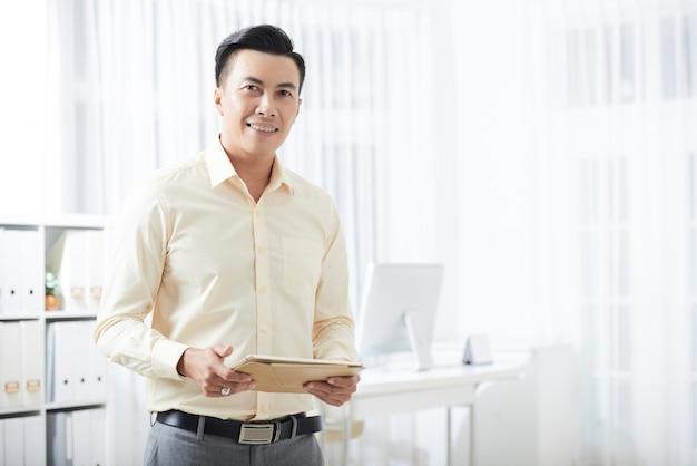 Glimlachende zakenman met tablet in bureau Gratis Foto