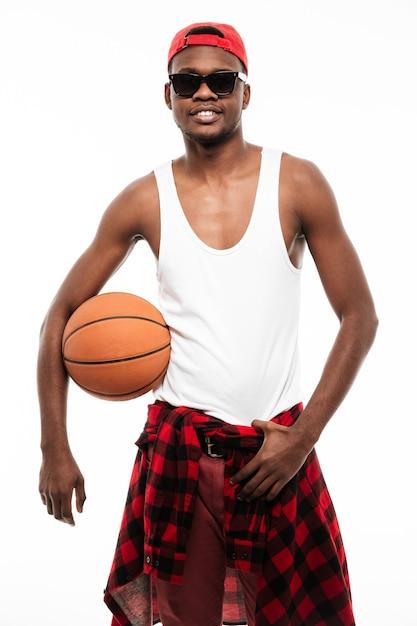 Glimlachende zekere jonge mens die en basketbalbal bevindt zich houdt Gratis Foto