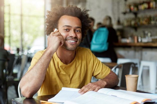 Glimlachende zwarte jongere zittend in cafetaria spreken via slimme telefoon met brede glimlach en goed humeur terwijl u rust Gratis Foto