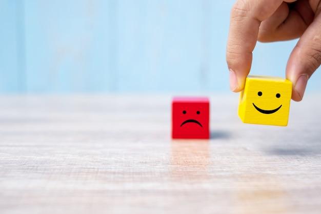 Glimlachgezicht op gele houten kubus. serviceclassificatie, rangorde, klantbeoordeling Premium Foto