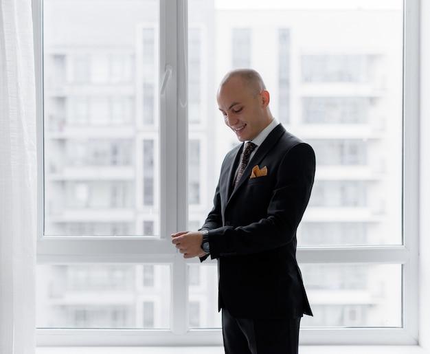 Glimlachte kale man verkleedt zich bij het raam in het stijlvolle pak voor een belangrijke zakelijke bijeenkomst Gratis Foto