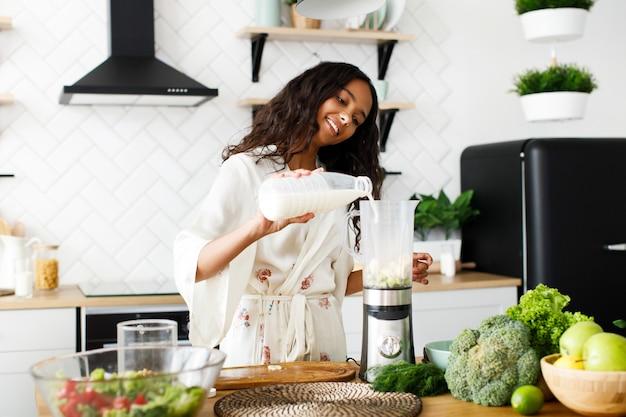 Glimlachte mooie mulatvrouw giet melk in de mixer dichtbij de lijst met verse groenten op witte moderne keuken gekleed in nachtkleding met los haar Gratis Foto