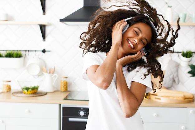 Glimlachte mulatvrouw met krullend haar in grote draadloze hoofdtelefoons danst gelukkig met haar ogen dicht in de moderne keuken Gratis Foto