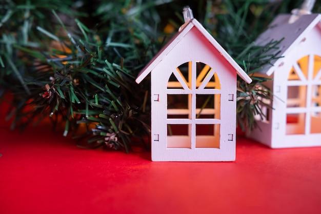 Gloeiende houten huisslinger op een kerstboom. kerst concept en onroerend goed concept Premium Foto