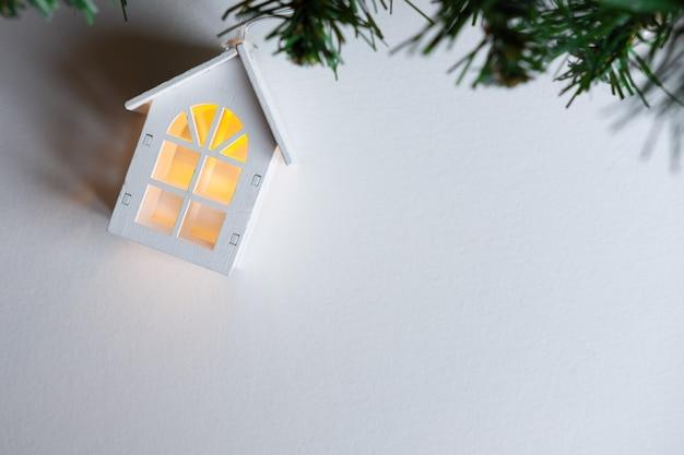 Gloeiende houten huisslinger op een kerstboom op een witte achtergrond. Premium Foto