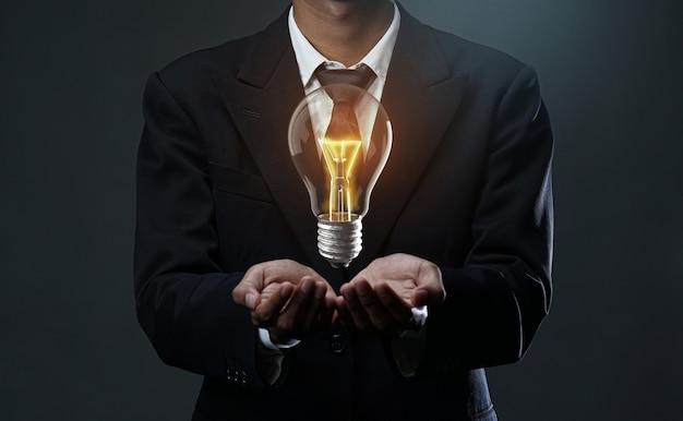 Gloeiende lamp die op zakenmanhand drijft. Premium Foto