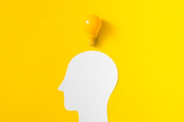 Gloeilamp over het verwijderde witte menselijke hoofd op gele achtergrond Gratis Foto