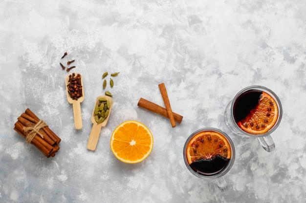 Glühwein glintwijn geserveerd in glazen voor kerst tafel met sinaasappel en kruiden Gratis Foto
