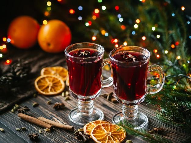Glühwein in glazen op de tafel versierd met een kerstboom. sinaasappelschijfjes, anijssterren, kardemom, kaneel Premium Foto