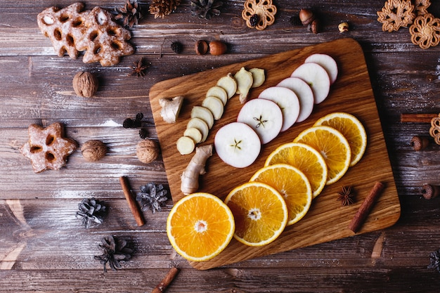 Glühwein koken. sinaasappelen, appels en soorten liggen op houten tafel Gratis Foto