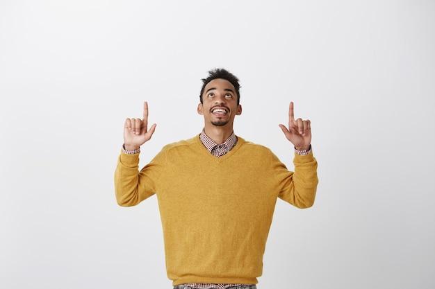 Godzijdank is het vrijdag. portret van tevreden geïnteresseerde jonge afro-amerikaanse student in stijlvolle gele trui handen opheffen, kijken en omhoog, genieten van mooi uitzicht op de hemel Gratis Foto