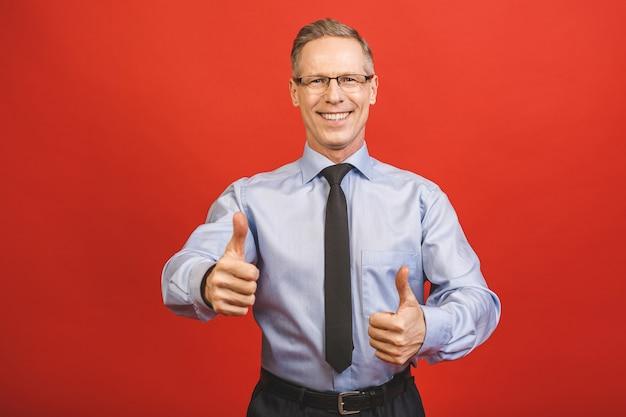 Goed gedaan! sluit omhoog portret van verrukkelijke zekere koele blije vrolijke opgewekte opgewekte oude hogere bedrijfsmens die duim op glimlach aantonen die op rode muur wordt geïsoleerd. Premium Foto