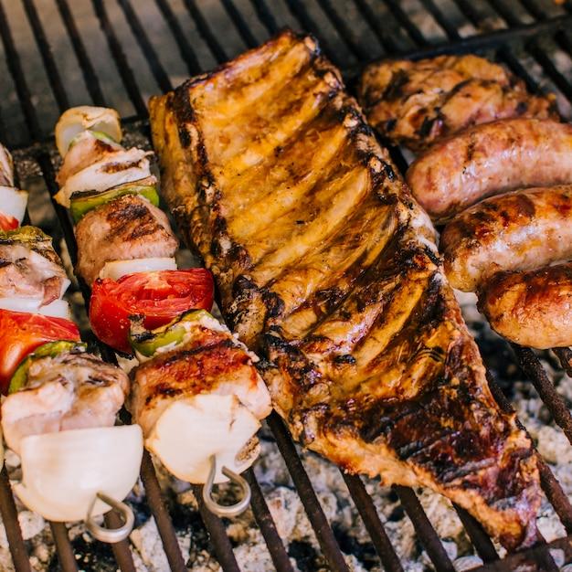Goed gegrilde stukjes vlees en groenten op grill houtskool Gratis Foto