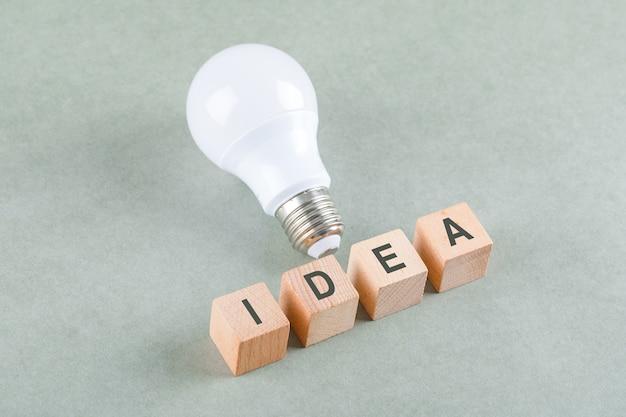 Goed idee concept met houten blokken met pictogrammen, grote lamp op salie kleur tabel hoge hoek bekijken. Gratis Foto