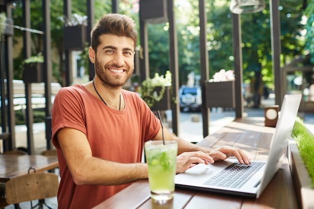 Goed uitziende, aantrekkelijke bebaarde man breed glimlachend op camera gekleed terloops zittend aan een houten tafel limonade drinken, surfen op high-speed internet op laptop pc. genieten van een zomerdag. Gratis Foto