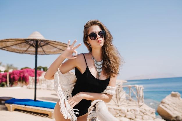 Goed uitziende gebruinde meid met mooie gezichtsuitdrukking poseren tijdens het rusten op zee strand in zomerochtend. geweldige brunette vrouw met ketting plezier op resort voor oceaan Gratis Foto